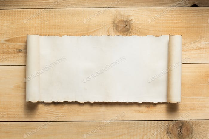 curved or scrolled paper on wooden background