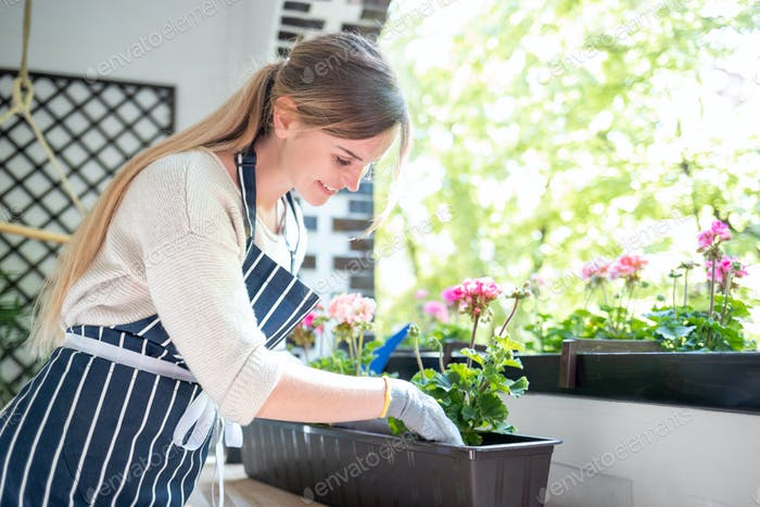 Beautiful woman among flowers at her balcony during planting