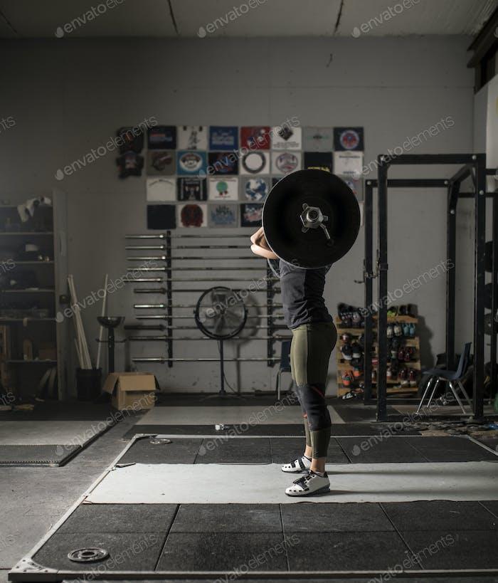 Levantador de  pesas Mujer anónimo con pesos pesados.