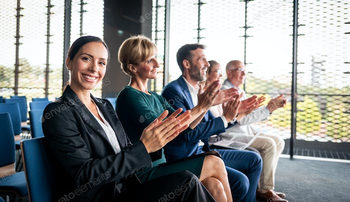 Happy audience applauding speaker at business conference