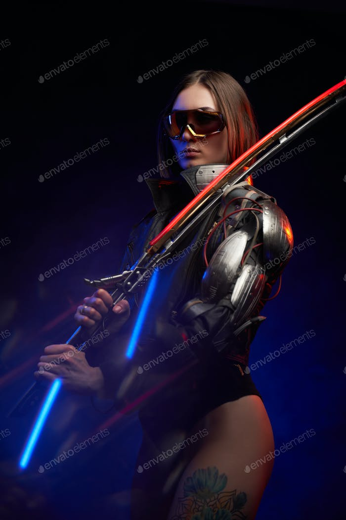 Seductive female soldier with sword and cybernetic hand in studio