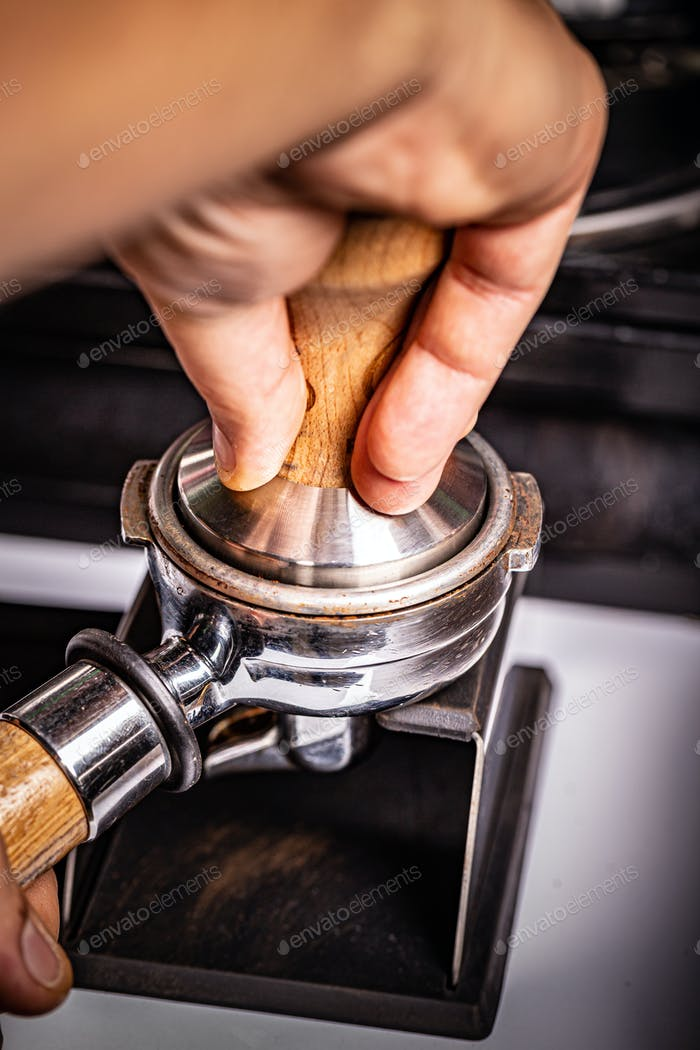 Barista presses ground coffee