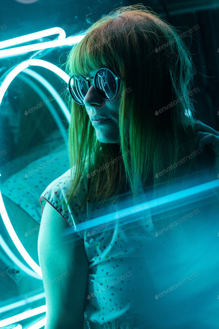 Cinematic Portrait of girl with sunglasses on neon lights and reflections on prism