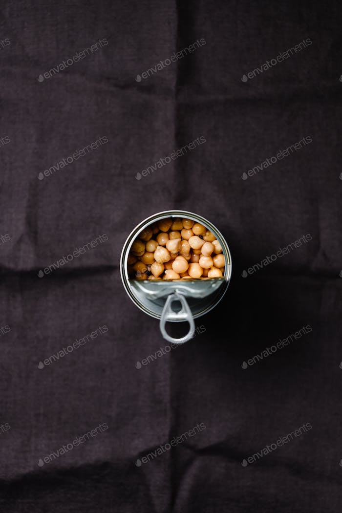 Opened can of chickpeas on a dark background.