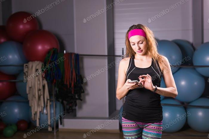 Mujer con rastreador de actividad y smartphone en gimnasio