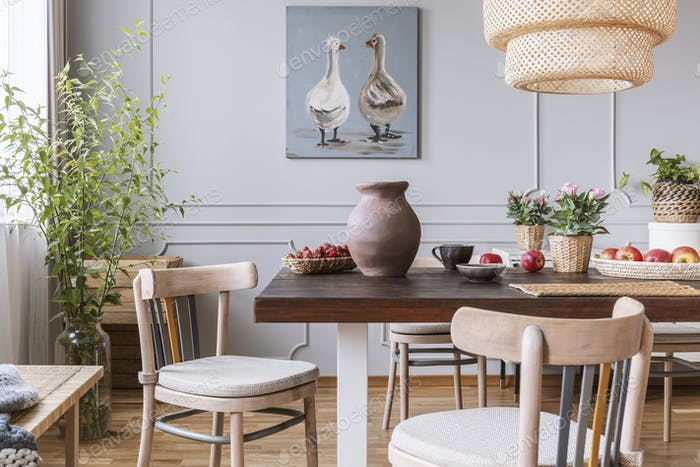 Wooden chairs at table with flowers in natural dining room inter
