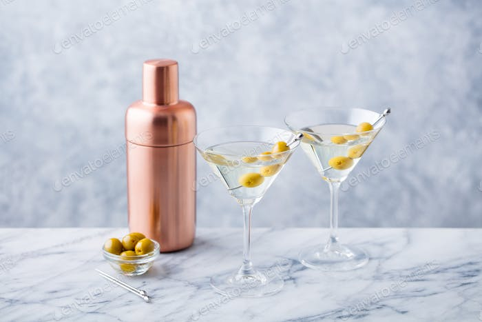 Martini Cocktail with Green Olives, Shaker on Marble Table Background