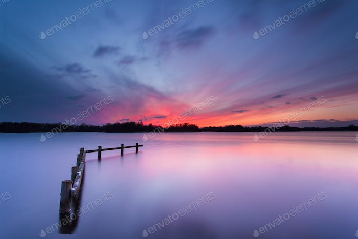Blue Sunset over Tranquil Lake with Wooden Mooring Post