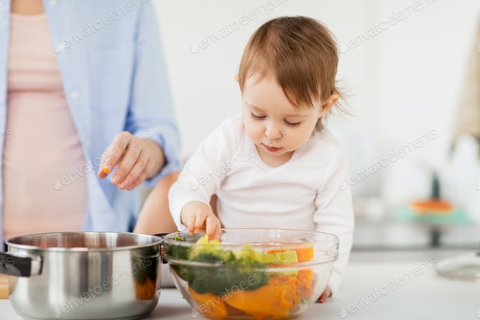 baby with vegetables and mother cooking at home