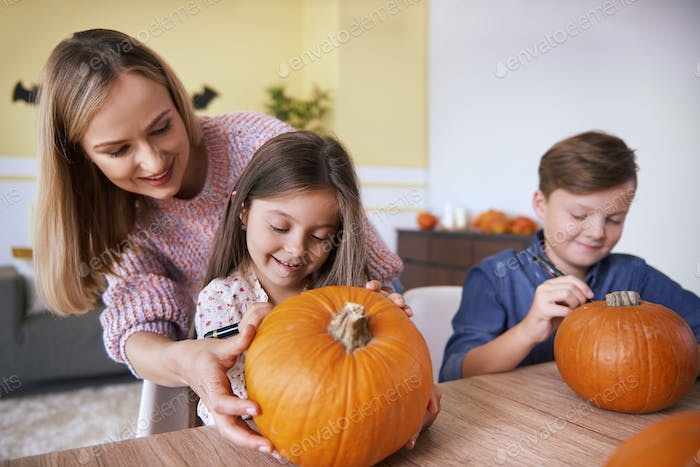 Mother and children drawing on pumpkin