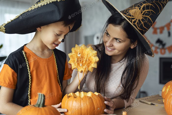 Mom with son making pumpkins for Halloween