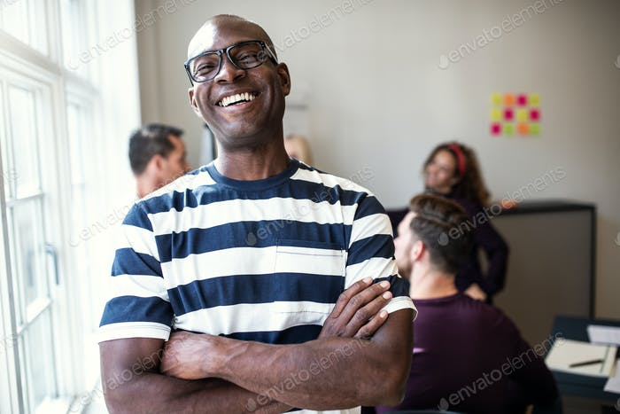 Laughing African designer standing in an office after a meeting