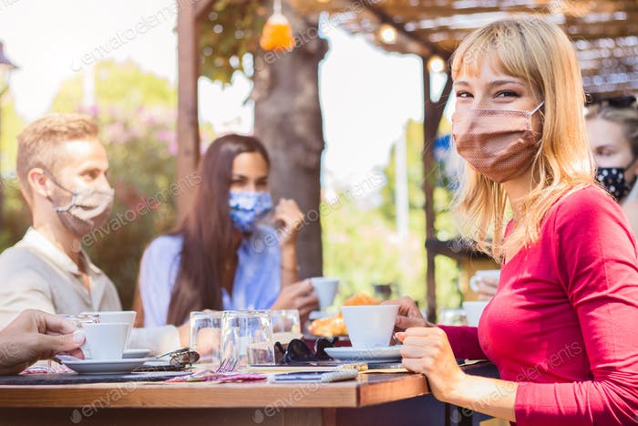 Happy young woman wearing face mask smiling at the camera at the restaurant cafè