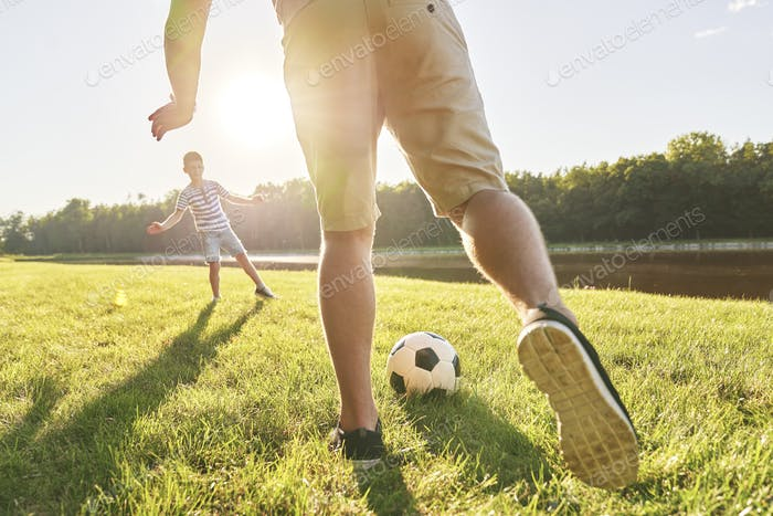 Father and son training soccer on holiday