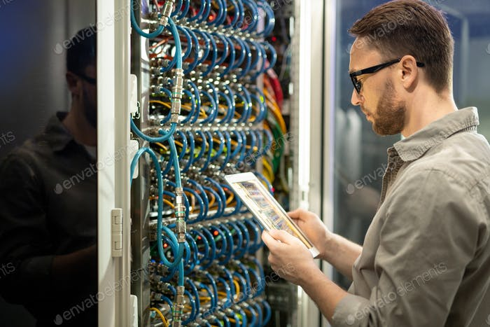 Data center technician checking connections on tablet