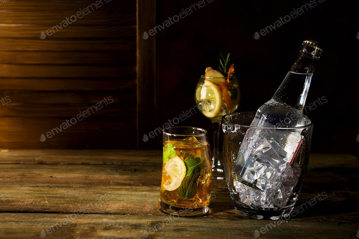 whiskey based cocktail with Glass ice bucket on dark wooden backgorund