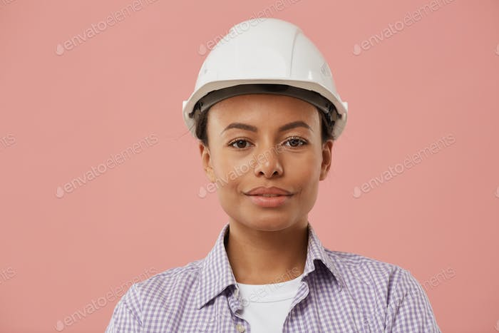 Young Woman Wearing Hardhat Posing on Pink