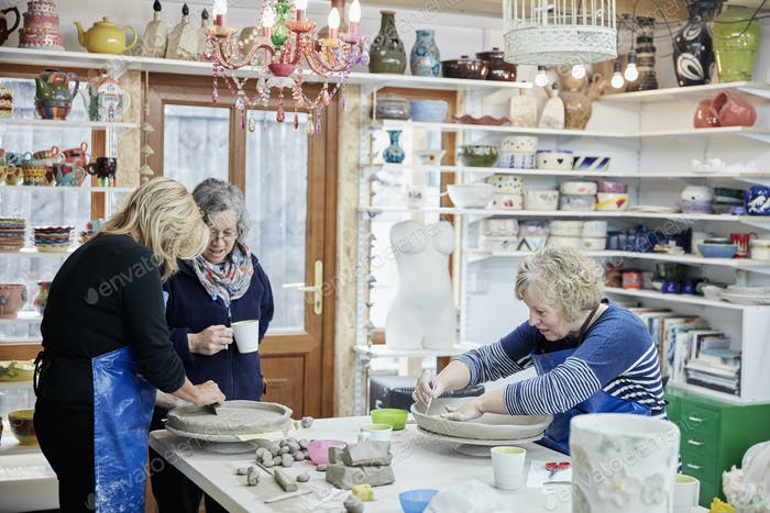 Three women in a pottery studio working with clay.