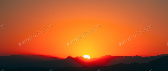 Sunshine Over Dark Silhouette Of Mountains During Sunrise. Sun Above Beautiful Mountains Landscape