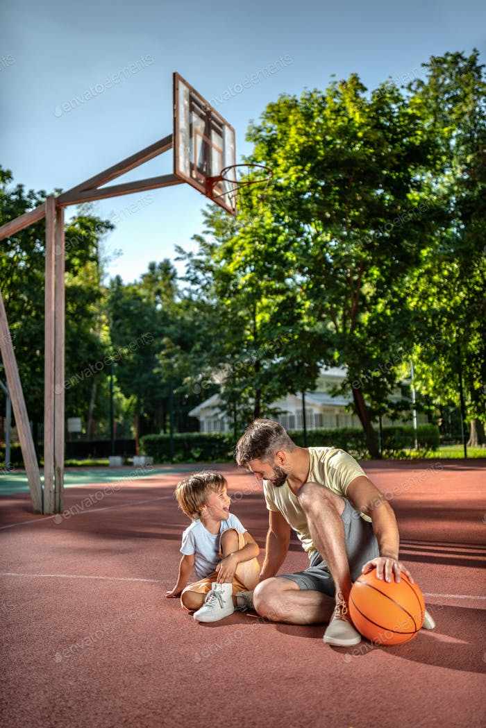 Father and son with a ball on the basketball court