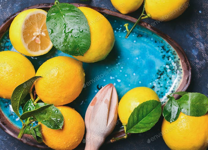Freshly picked lemons with leaves and pounder in blue plate