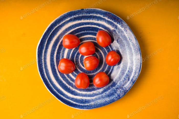 Cherry tomatoes plate on yellow wooden table. Top view