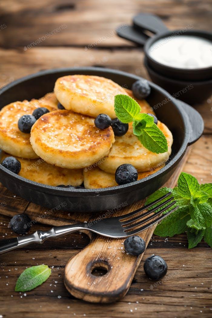 Köstliche Hüttenkäse Pfannkuchen oder Syrniki mit frischer Heidelbeere in gusseiserner Pfanne