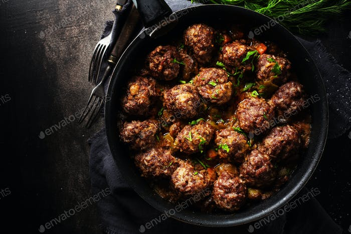 Fried meatballs with sauce on pan