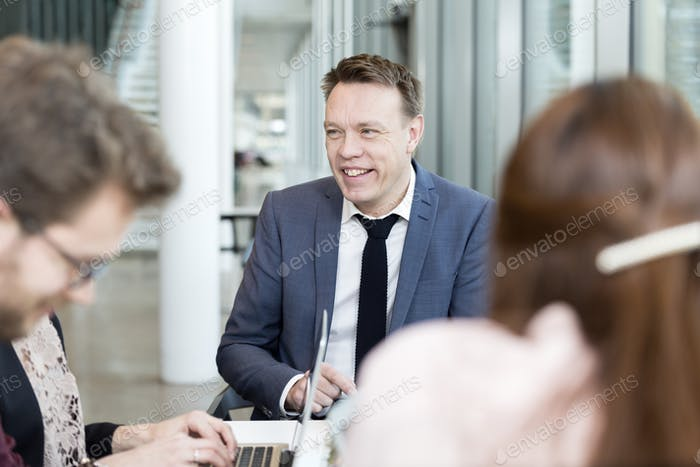 Happy businessman communicating with coworkers in meeting at office