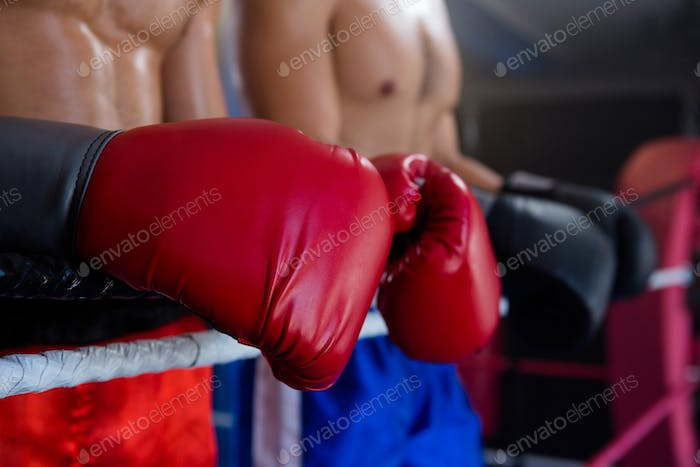 Midsection of male boxers standing by rope