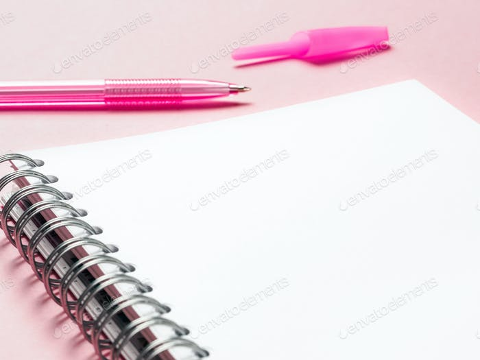 blank note with pen on pink background