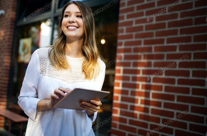 Beautiful young woman using tablet in the city