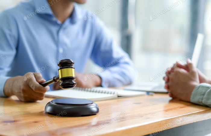 Primer plano de Abogado sosteniendo un martillo dando consejos sobre la ley, Concepto de justicia.