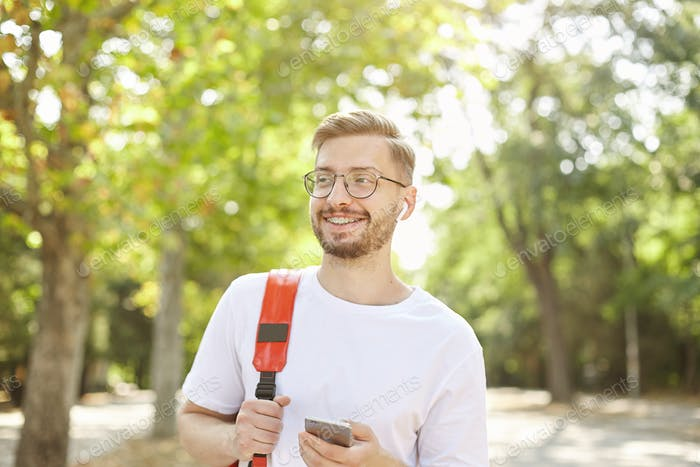 Portrait of good looking happy male with mobile in hand, looking away and smiling broadly