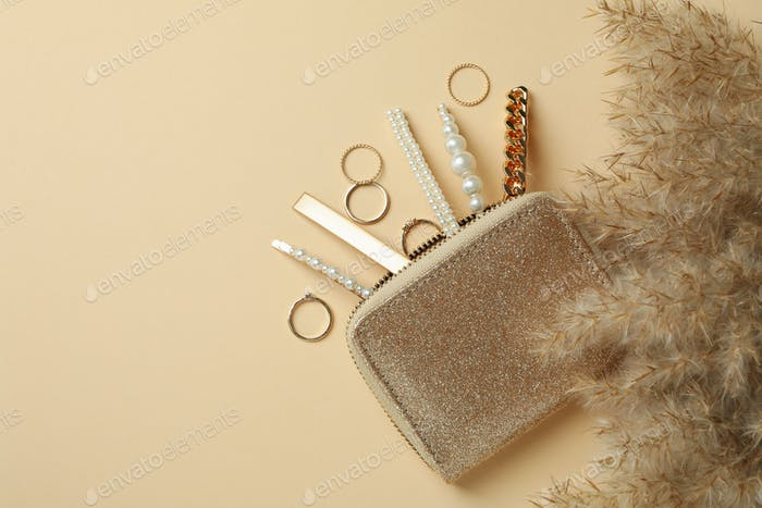 Cosmetic bag with jewelry and reeds on beige background