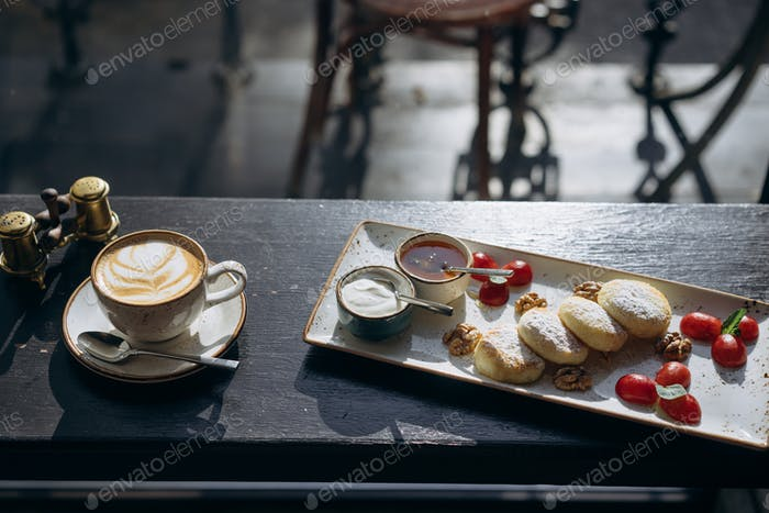 Cottage cheese pancakes with sour cream, honey on a tray and latte