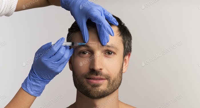 Mature Man Receiving Cosmetic Injection Standing Over White Background, Panorama