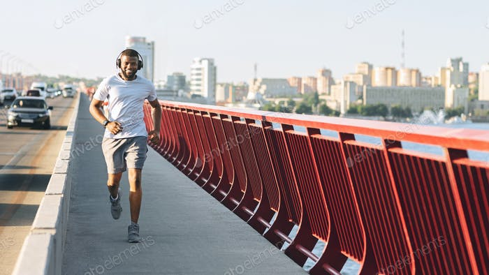 Afro athlete enjoying running along city highway
