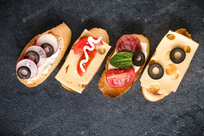 Open faced sandwich canape or crostini on dark stone background closeup. Top view.