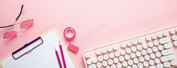 Компьютерная клавиатура и канцелярские принадлежности на розовом фоне