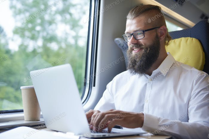 Businessman with beard working during the journey