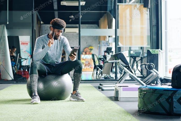 Mann sitzt auf Gymnastikball mit Smartphone