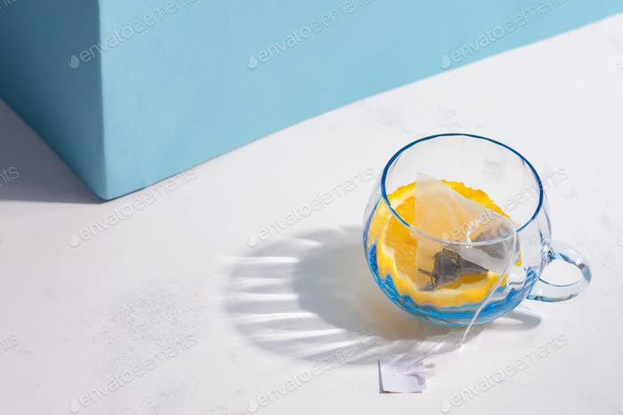 Glass cup with fruit tea bag and slice of lemon on a white table with shadow against pastel blue