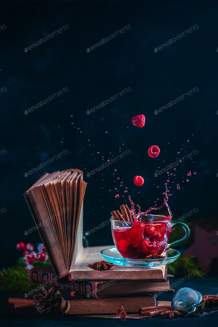 Red berry tea on a stack of books with a dynamic splash. Winter hot drink on a dark background with