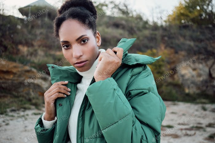 Attractive serious African American girl in down jacket intently looking in camera outdoor