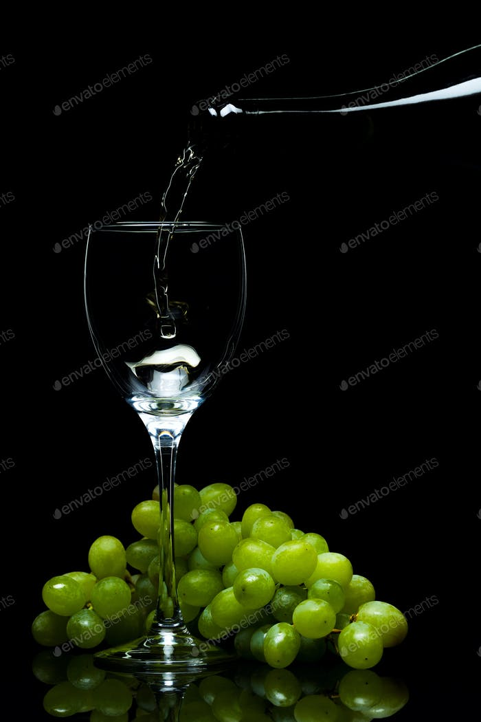 Glass of wine, grapes, wine, flowing from a bottle, black background