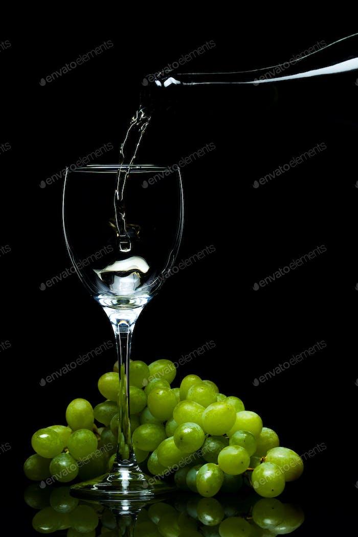 Glas Wein, Trauben, Wein, fließt aus einer Flasche, schwarzer Hintergrund