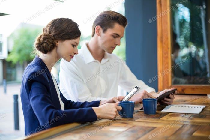 Businessman and woman using mobile phone and digital tablet at counter