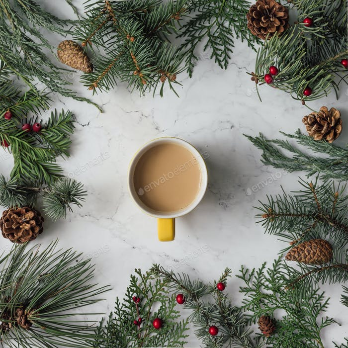 Creative arrangement of Christmas winter foliage with tea cup. Holiday background. Flat lay.