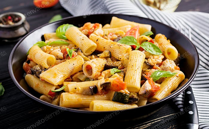 Rigatoni pasta with chicken meat, eggplant in tomato sauce in bowl. Italian cuisine.